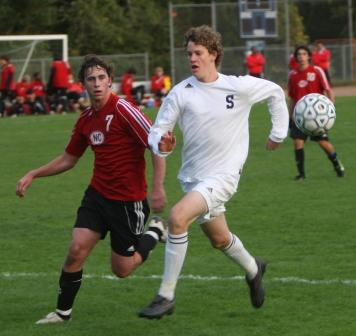 Nathan Greenberg and a New Canaan defender move forward, though the ball has not yet arrived.  (Photo by Carl McNair)