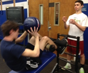 Freshmen James Lewis and Joe Pravder strengthen their abs, with a heavy ball.