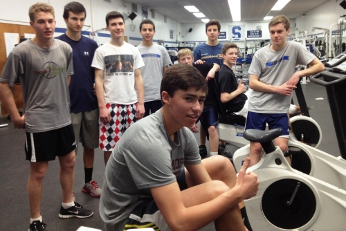 Nate Argosh shows off the new Concept2 rowing machine. Watching him during an early morning workout are (from left) Daniel Boyce, James Rubin, Ryan Ruggiano, Noah Schwaeber, Matt Bateman, Diego Alanis, Michael Reid and Patrick Beusse.